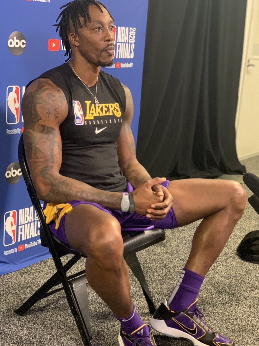 Lakers center Dwight Howard, in some purple-and-gold Kobe shoes by Nike, takes a break.