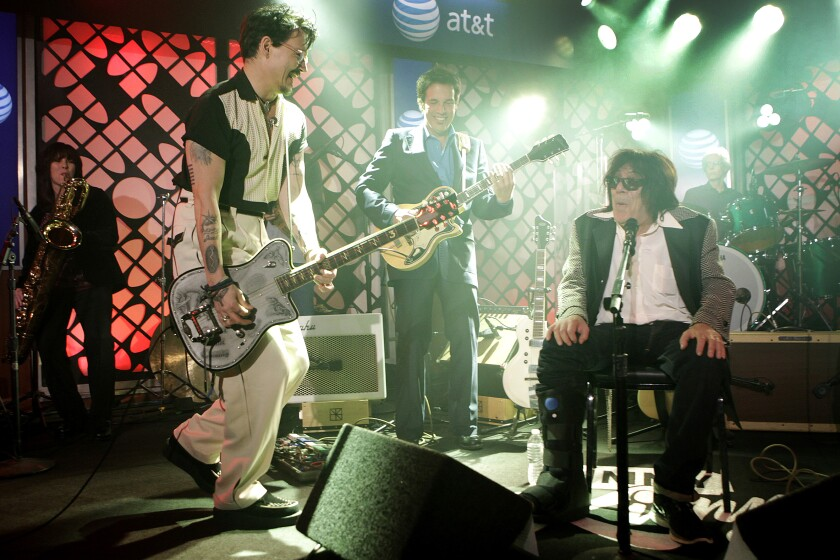 Two men play guitars with a band while a man sits at a microphone