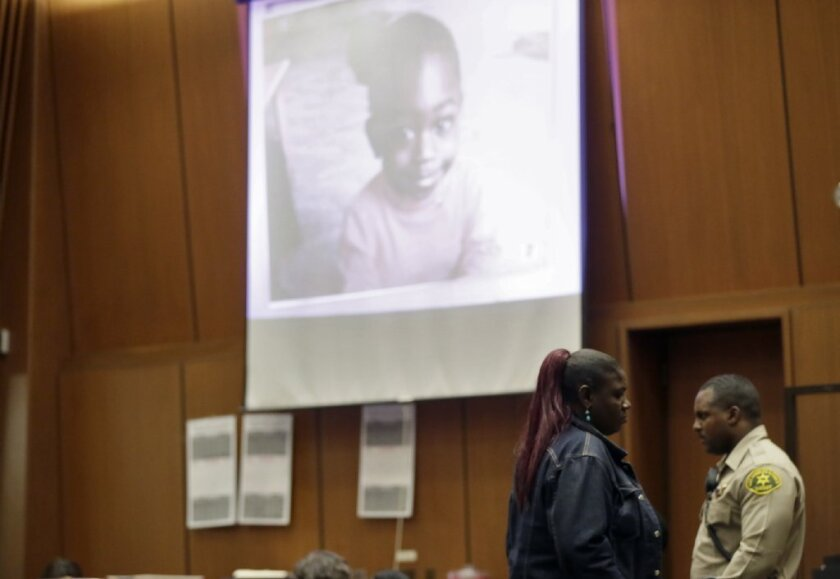 Olivia Vanclief walks past the projected image of her daughter Viola after testifying for the prosecution against Kiana Barker, who was convicted in October of second-degree murder in the two-year-old's 2010 beating death. Despite a record of violence, the child was placed with Barker by United Care, a private foster care agency.