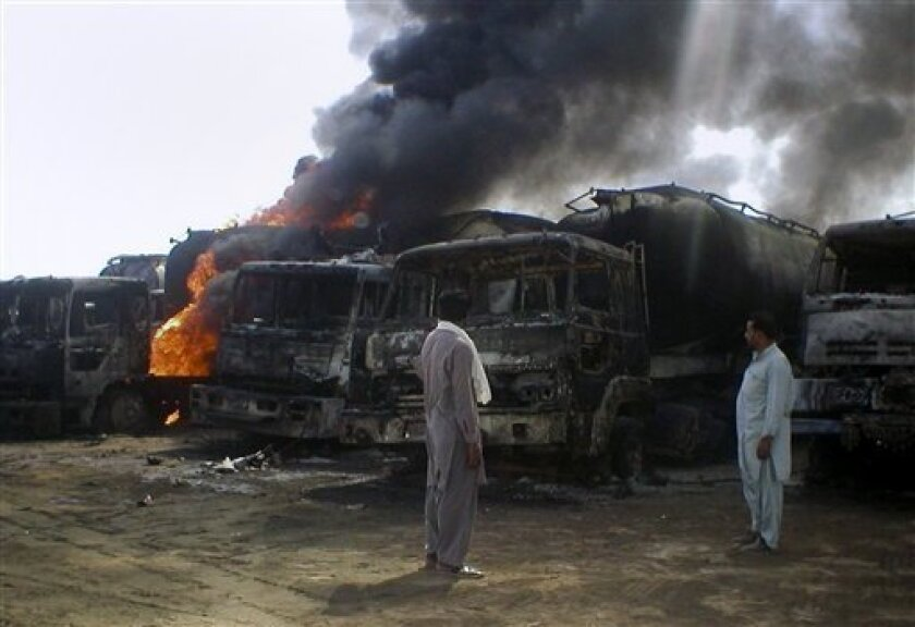 Local residents look to burning oil tankers after a militant attack in Mithri, about 200 kilometers (120 miles) east of Quetta, Pakistan on Saturday, Oct. 9, 2010. Gunmen armed with a rocket torched 29 NATO oil tankers in southwestern Pakistan before dawn Saturday, the latest attack on the supply line for international troops in Afghanistan since Pakistani authorities closed a key border crossing amid a dispute with the United States. (AP Photo)