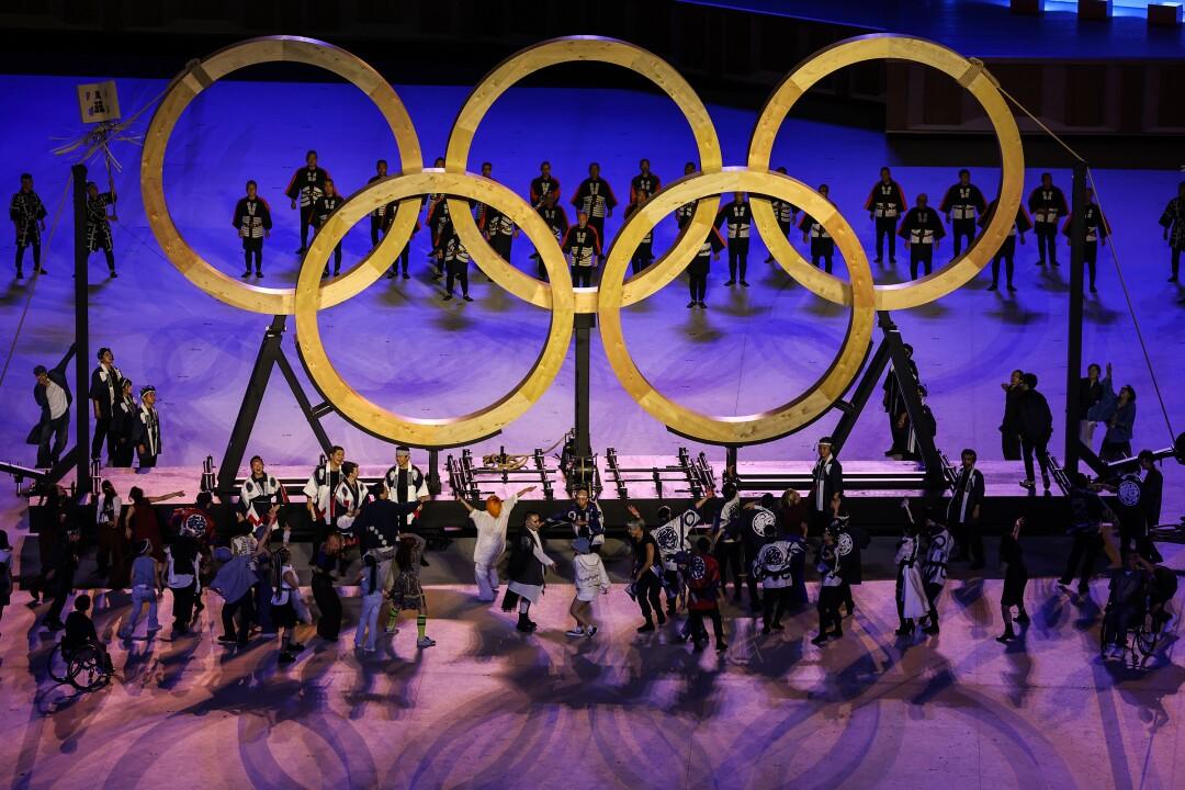 مجریان حلقه های المپیک را روی صحنه احاطه می کنند