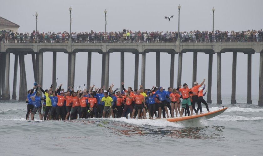 Crowds in Huntington Beach watch from the pier as surf champions, celebrities and locals break the Guinness record for most people on a surfboard (66).