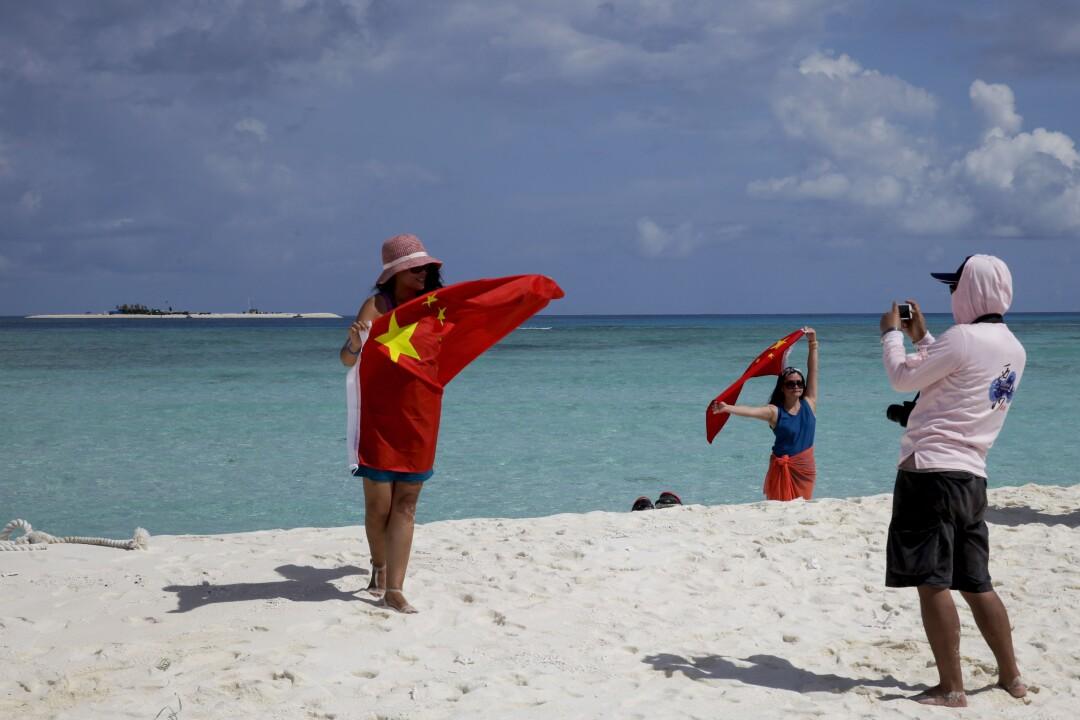 Die Menschen halten die rote chinesische Flagge an einem weißen Sandstrand