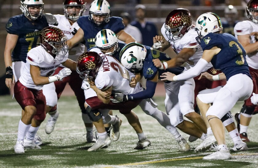 Mission Hills running back Cameron Woolsey is tackled by several La Costa Canyon defenders.