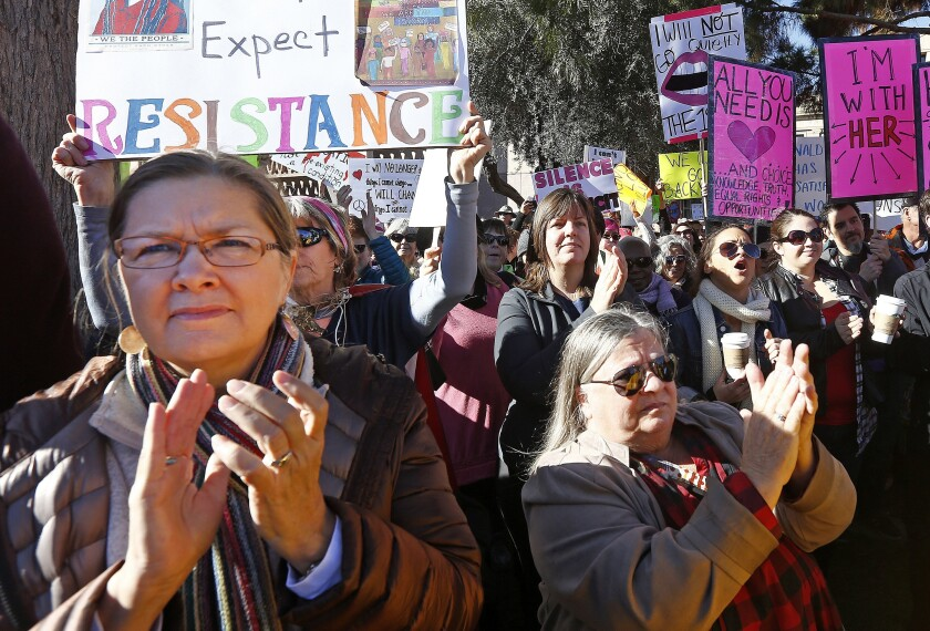 Demonstrators applaud speakers in support of the Women's March on Washington at the Arizona Capitol.