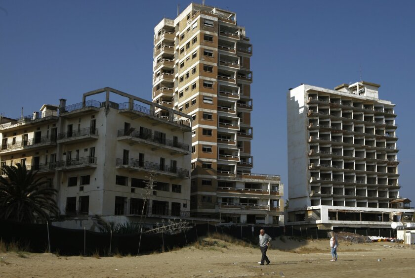 A couple walk on the beach by the deserted hotels in an area used by the Turkish military in the Turkish occupied area in the abandoned coastal city of Varosha, in Famagusta, in southeast of island of Cyprus, Friday, Jan. 17, 2014. Time virtually stopped in 1974 for the Mediterranean tourist playgr