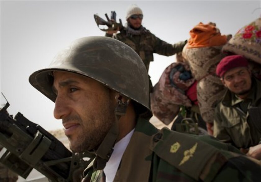 Libyan rebels stop at a checkpoint in Al-Egila, east of Ras Lanuf, eastern Libya, Sunday, March 27, 2011. The rebels claim that they have entered Ras Lanuf. The rebels claim that they have entered Ras Lanuf. Libyan rebels took back a key oil town and pushed westward Sunday toward the capital, seizing momentum from the international airstrikes that tipped the balance away from Moammar Gadhafi's military. Brega, a main oil export terminal in eastern Libya, fell after a skirmish late Saturday and rebel forces moved swiftly west, seizing the tiny desert town of Al-Egila a collection of houses and a gas station on their way to the massive oil refining complex of Ras Lanouf. (AP Photo/Anja Niedringhaus)