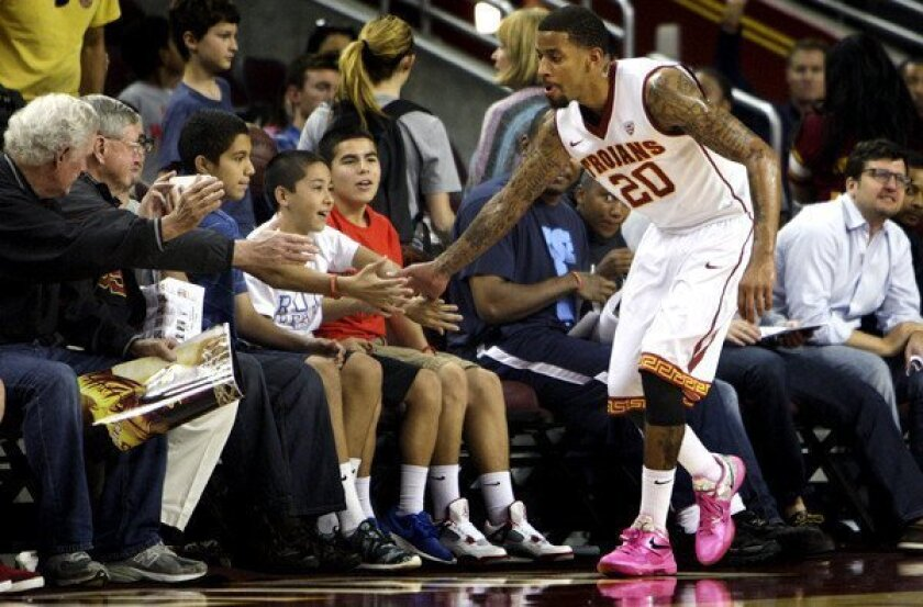USC guard J.T. Terrell high-fives fans courtside after a scrimmage at Galen Center.