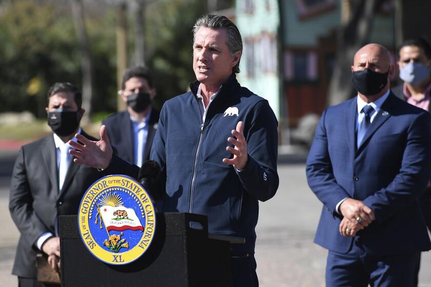 California Gov. Gavin Newsom, center, gestures in front of local officials.