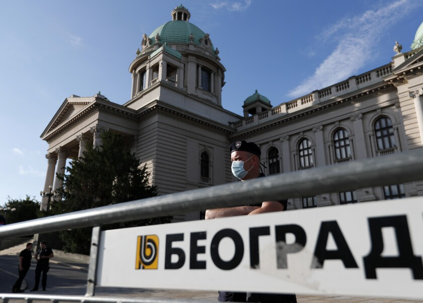 """A police officer, wearing a mask to protect against coronavirus, guards the Serbian parliament building during a protest against President Aleksandar Vucic and his government, in Belgrade, Serbia, Saturday, June 20, 2020. Sign in front reads """"Belgrade"""" in Serbian Cyrillic letters. Serbia is holding a parliamentary vote this weekend that takes place amid concerns over continuing spread of the new coronavirus and deep political divisions in the Balkan country. The ruling populist of President Aleksandar Vucic are expected to cement their grip on power at Sunday's balloting, facing practically no challenge from the opposition parties despite Serbia's plummeting democracy record and mounting allegations of corruption. (AP Photo/Darko Vojinovic)"""