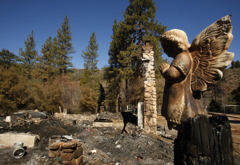 A ceramic angel stands watch over the charred debris at the cabin on Seven Oaks Road in Angelus Oaks where murder suspect and former cop Christopher Dorner died after a shootout with police.