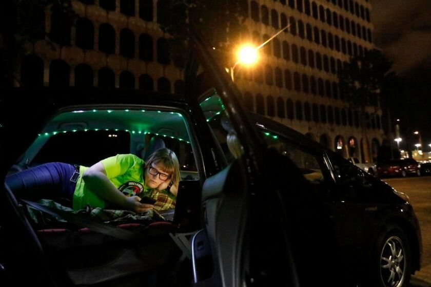 Jos Cashone, 28, looks at her phone in May before bedding down for the night in her car, which she also uses for her job as a Lyft driver.