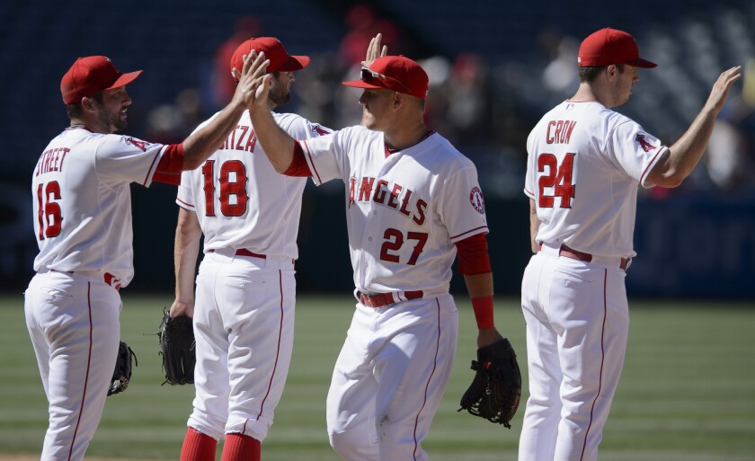 Mike Trout (27) celebrates with pitcher Huston Street, left, after the Angels' 13-7 victory over the Texas Rangers on July 26 at Angel Stadium.