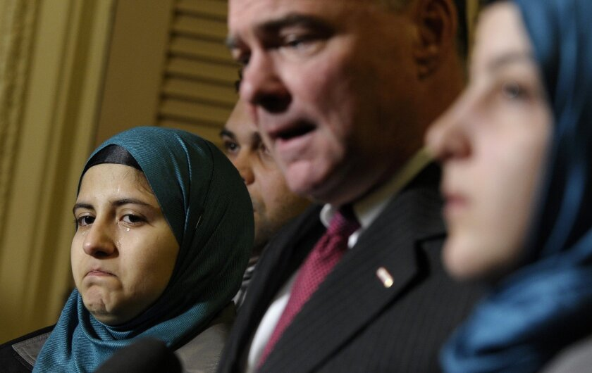 Sen. Tim Kaine, D-Va., chairman of the Senate Foreign Relations subcommittee on Near Eastern, Southern and Central Asian Affairs, second from right, speaks as Heba Sawan, left, tears up during a news conference with sister Amineh Sawan, right, and Anas al-Dabas, second from left, on Capitol Hill in Washington, Thursday, Feb. 6, 2014. The Sawan sisters were survivors of the August 2013 chemical weapons attack in Moadamiya, Syria that left more than 1,200 Syrians dead and many more wounded. Al-Dabas witnessed the 2012 massacre in Daraya that took the lives of 540 Syrians. (AP Photo/Susan Walsh)
