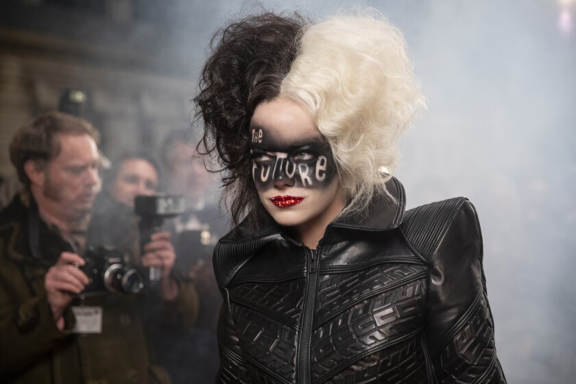 """Emma Stone with half-white, half-black hair, a black jacket and the words """"The Future"""" painted like a mask on her face"""