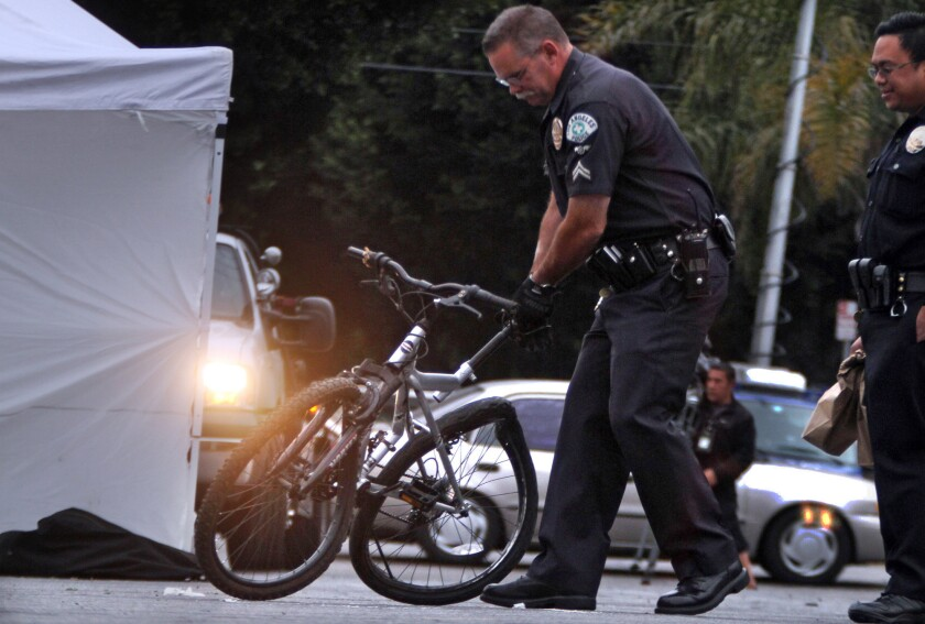 A police officer removes a bicycle whose rider was killed when he was struck by a car fleeing police after a shooting incident in Florence, authorities said.