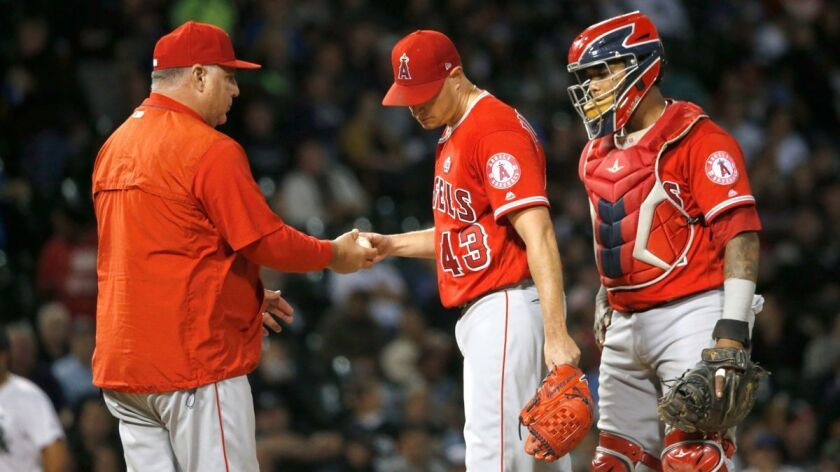 Angels manager Mike Scioscia, left, takes starting pitcher Garrett Richards out of the game as catcher Martin Maldonado watches during the fourth inning against the Chicago White Sox on Wednesday.