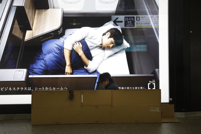 A homeless man sits in a cardboard box