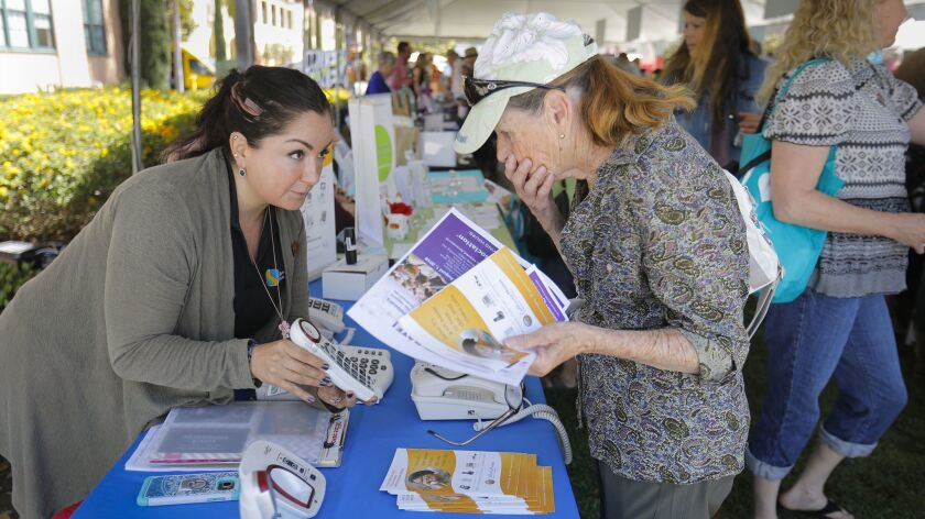 Sandra Lambarri-Johnson, left, an outreach specialist with the California Telephone Access Program, discusses different phones with Felicia Roberto, right, of El Cajon, during the CaregiverSD Community Expo at Liberty Station.