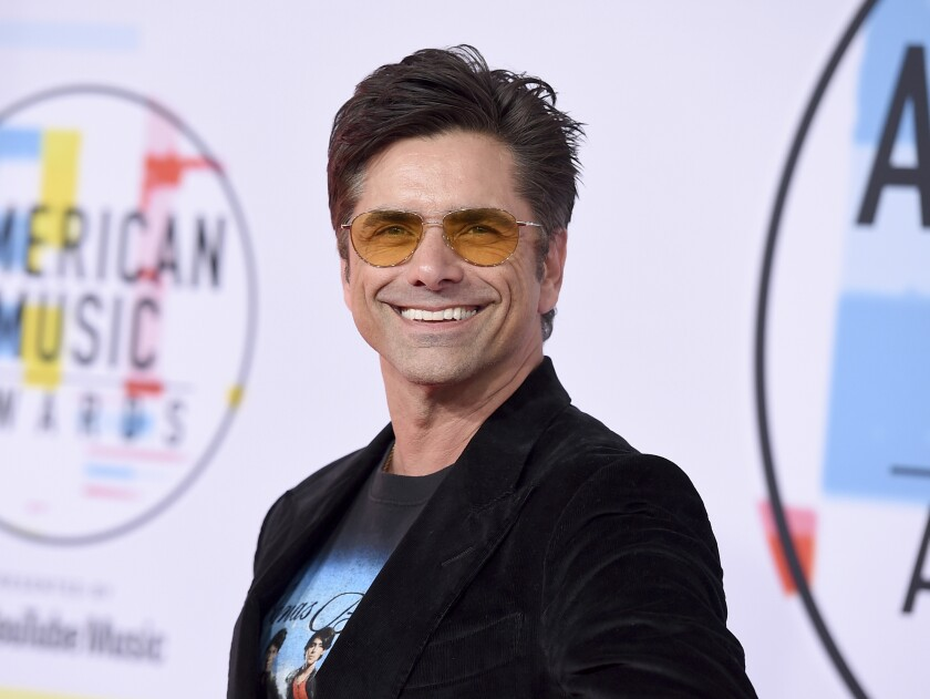 A smiling man with short brown hair and yellow-lens sunglasses