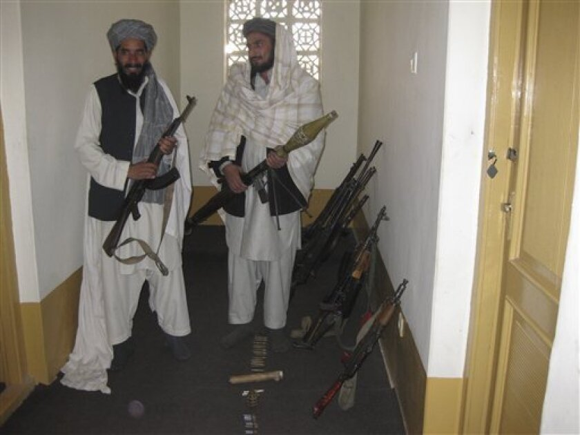 This photo taken Jan. 31, 2010 shows Qari Mohebulla Nakarar, left, and Fazel Rahman Farouqi, former pro-Taliban fighters, pose for a photograph while holding their newly-surrendered Soviet-era weapons, at an Afghan government-run reconciliation office, in Jalalabad, Nangarhar province, east of Kabul, Afghanistan. Farouqi, who fled Afghanistan after the fall of the Taliban in 2001 and led a cell attacking NATO supply convoys in Pakistan, said he was willing to take a chance on reconciliation. If he gets what was promised, especially immunity from prosecution, he believes hundreds of his comrades may follow. (AP Photo/Amir Shah)
