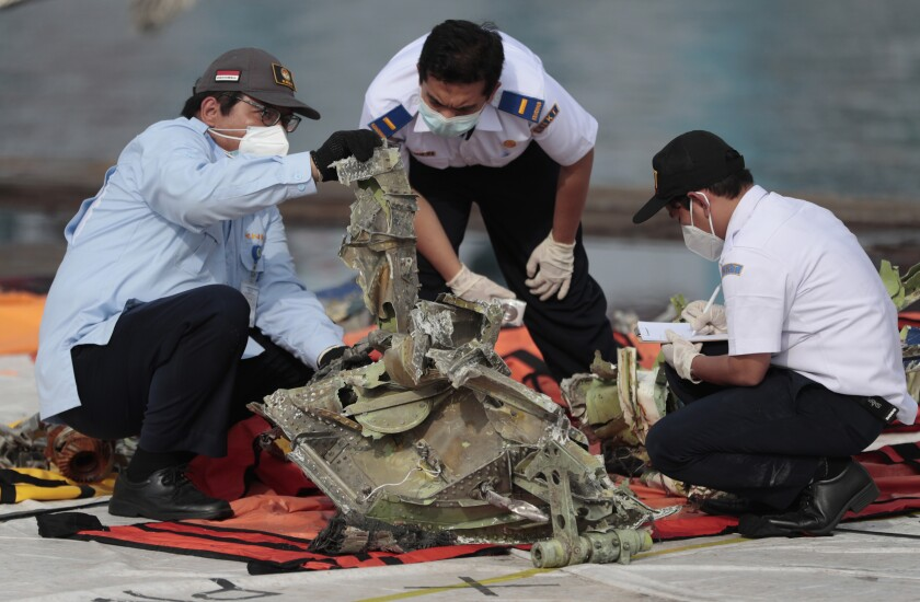 FILE - In this Jan. 21, 2021, file photo, investigators inspect a pieces of the Sriwijaya Air flight SJ-182 retrieved from the Java Sea where the passenger jet crashed on Jan. 9, at Tanjung Priok Port in Jakarta, Indonesia. A lawsuit filed in Seattle against Boeing alleges a malfunctioning autothrottle system on the older 737 jet led to the January crash of the Sriwijaya Air flight that killed all 62 people on board. (AP Photo/Dita Alangkara, File)