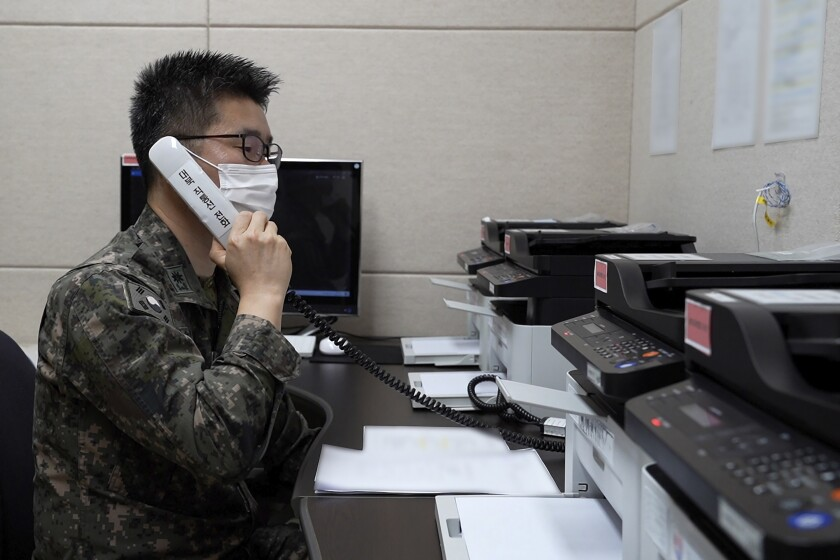 In this photo provided by South Korean Defense Ministry, an unidentified South Korean military officer makes a test call with a North Korean officer through an inter-Koran military communication line at an undisclosed location near the demilitarized zone, South Korea, Monday, Oct. 4, 2021. North Korea restored dormant communication hotlines with South Korea in a small, fragile reconciliation step Monday in an apparent hard push to win outside concessions with a mix of conciliatory gestures and missile tests. (South Korea Defense Ministry via AP).