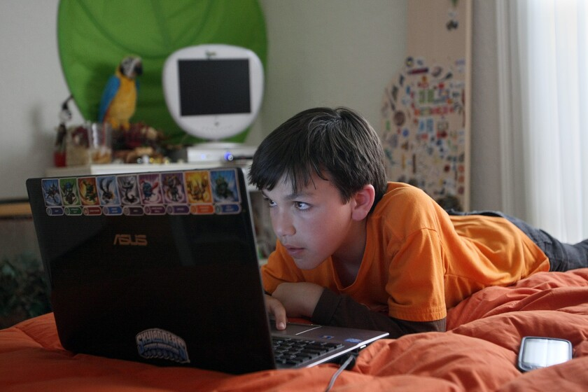 Friedman, Gary -- B582130423Z.1 LOS ANGELES, CALIF. - MAY 31, 2012: Cole Chanin-Hassman, 10, looks at a computer game call Minecraft on his laptop in his Brentwood home on May 31, 2012. Minecraft is a game which teaches Cole to build cities and other programs. Cole uses multiple devices such as the computer, phone, tv X-Box, Ipad, sometimes at one time and other times separate. (Gary Friedman/Los Angeles Times)