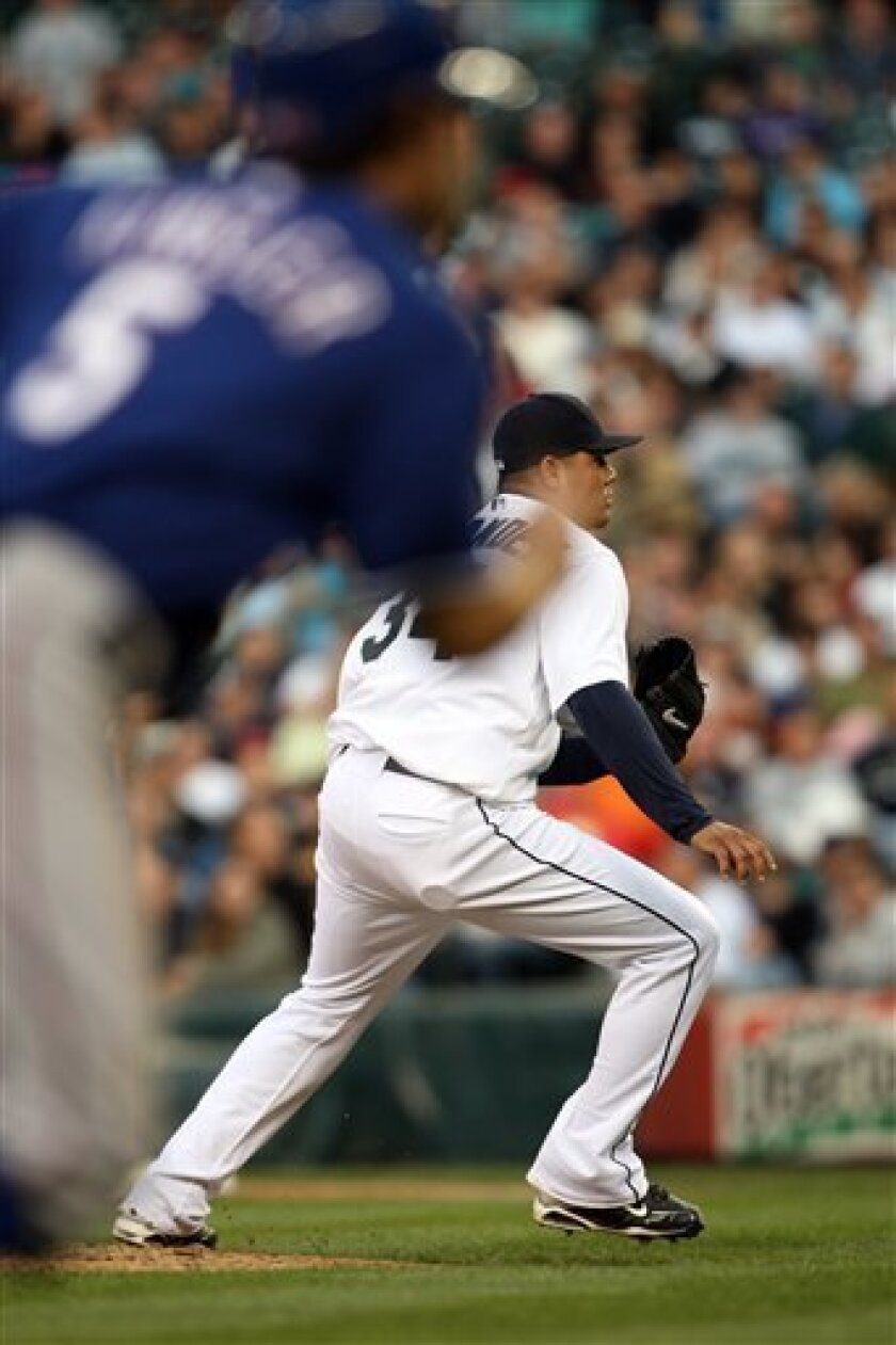 Seattle Mariners' pitcher Felix Hernandez, right, runs to cover homeplate as Texas Rangers' Ian Kinsler, left, runs home scoring a run on a wild pitch during the sixth inning of a baseball game in Seattle, on Thursday, July 9, 2009. (AP Photo/Kevin P. Casey)