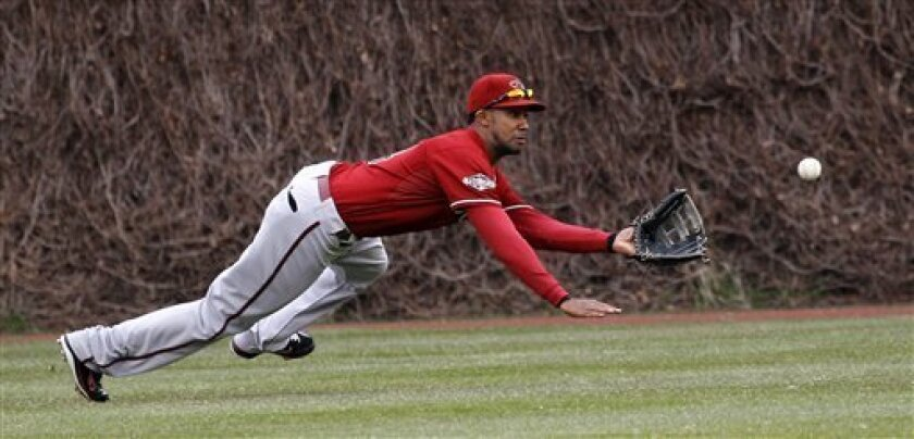 Arizona Diamondbacks center fielder Chris Young makes a diving catch on a fly ball hit by Chicago Cubs' Starlin Castro, during the first inning of a baseball game Wednesday, April 6, 2011 in Chicago. (AP Photo/Charles Rex Arbogast)