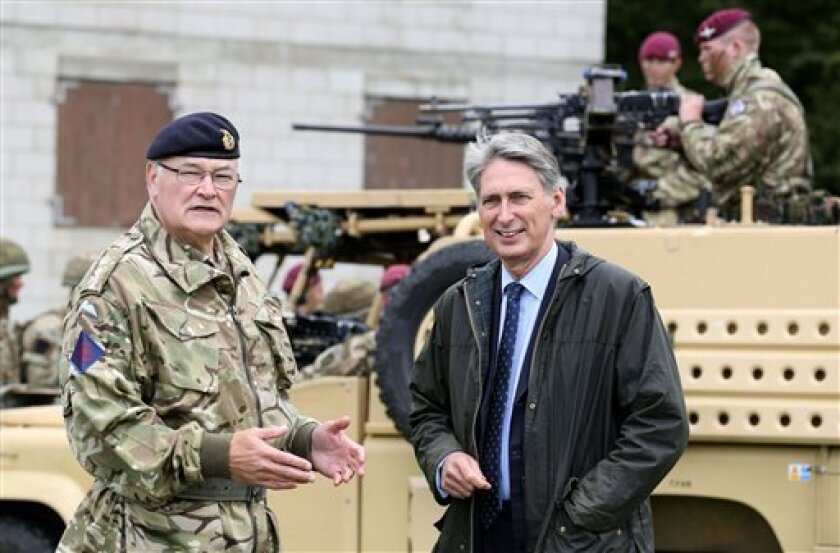 British Defence Secretary Philip Hammond, and Chief of the General Staff Sir Peter Wall, during a visit to Fingringhoe Ranges, in Colchester, Essex, in this Saturday June 22, 2013 photo. Hammond announced Wednesday July 3 2013 that army reservists will get military pensions and other benefits as part of a government bid to boost reserve numbers. The proposals come as Britain cuts its regular army from 100,000 to just over 80,000 soldiers and increases its army reservists to 30,000 by 2018, fr