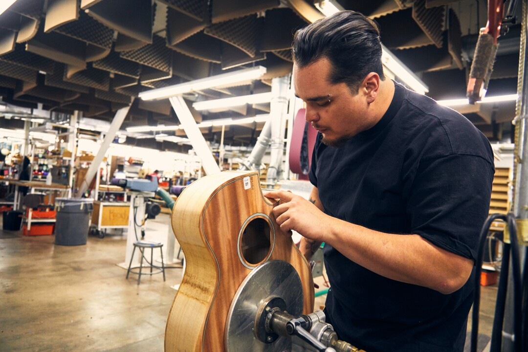 At Taylor Guitars' El Cajon facility, Clinton Jackson works on a guitar made out of urban wood.