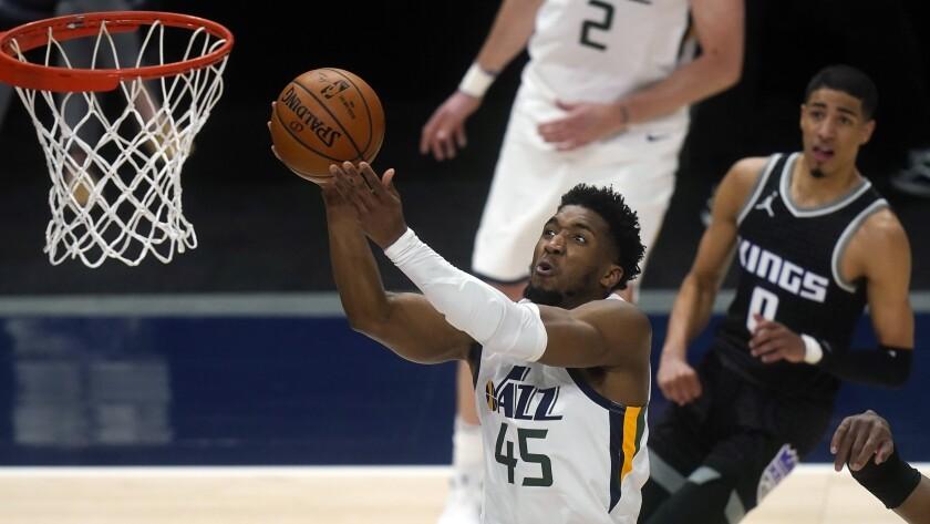 Utah Jazz guard Donovan Mitchell (45) goes to the basket as Sacramento Kings guard Tyrese Haliburton (0) looks on in the second half during an NBA basketball game Saturday, April 10, 2021, in Salt Lake City. (AP Photo/Rick Bowmer)