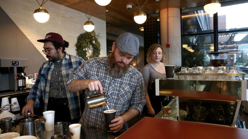 Ryan Murphy, left, manager of Stumptown Coffee Roasters, works with baristas Eric Perez and Sophie Fishman to handle a morning rush of customers. Stumptown opened in December in the Ace Hotel in Chicago's Fulton Market district, across from Google Chicago's headquarters.