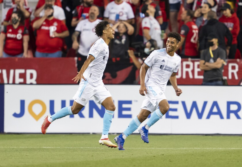 New England Revolution's Tajon Buchanan, left, celebrates with Brandon Bye after Buchanan scored during the first half of an MLS soccer match against Toronto FC on Saturday, Aug. 14, 2021, in Toronto. (Mark Blinch/The Canadian Press via AP)