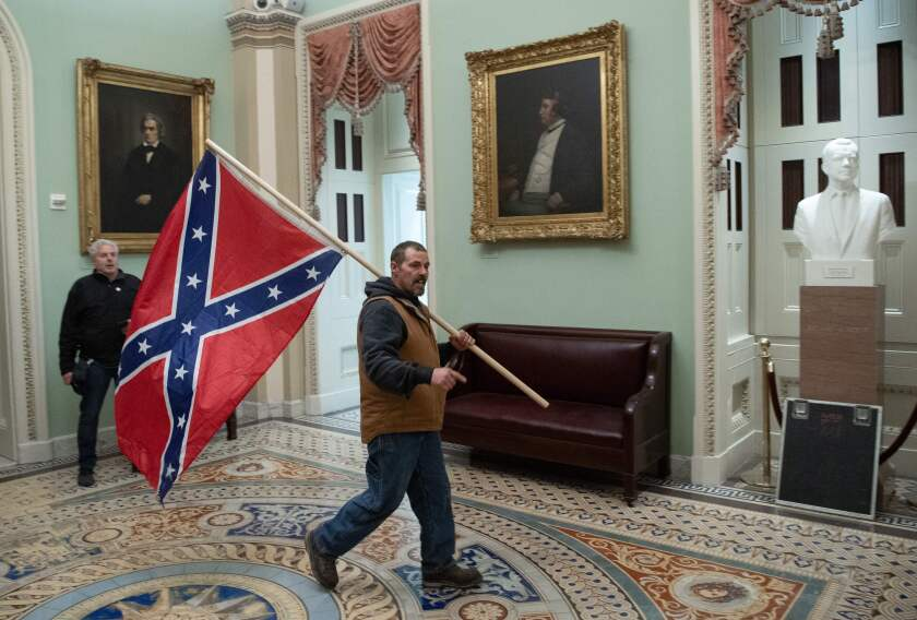 A man walking in the Capitol Rotunda carries a Confederate flag over his shoulder