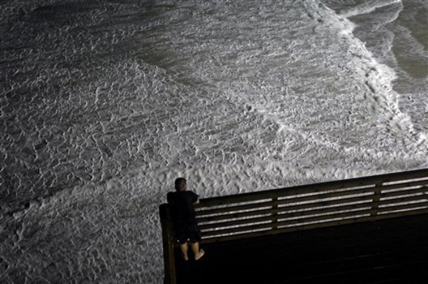 Waves surround an ocean-front hotel deck as a man looks on while Hurricane Earl passes offshore in Nags Head, N.C., Friday, Sept. 3, 2010. (AP Photo/Gerry Broome)