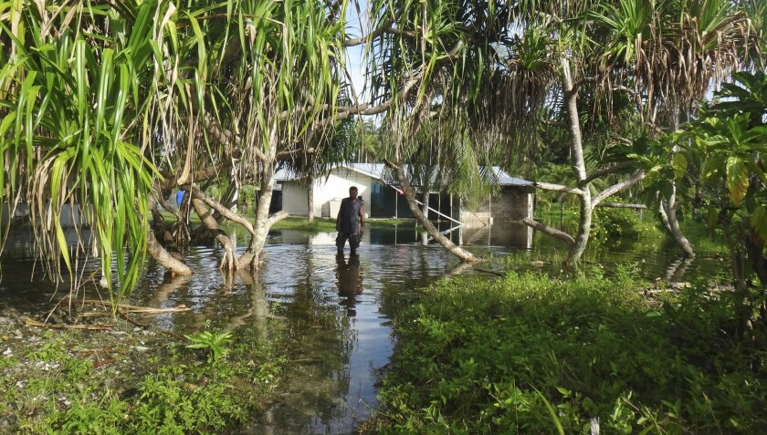 A man walks through knee-deep water to reach his home during a king tide event in 2015 on Kili in the Marshall Islands, where climate change poses an existential threat.