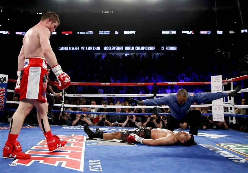 """El boxeador mexicano Saúl """"Canelo"""" Alvarez, izquierda, observa a Amir Khan tras noquearlo en un combate el 7 de mayo de 2016 en Las Vegas."""