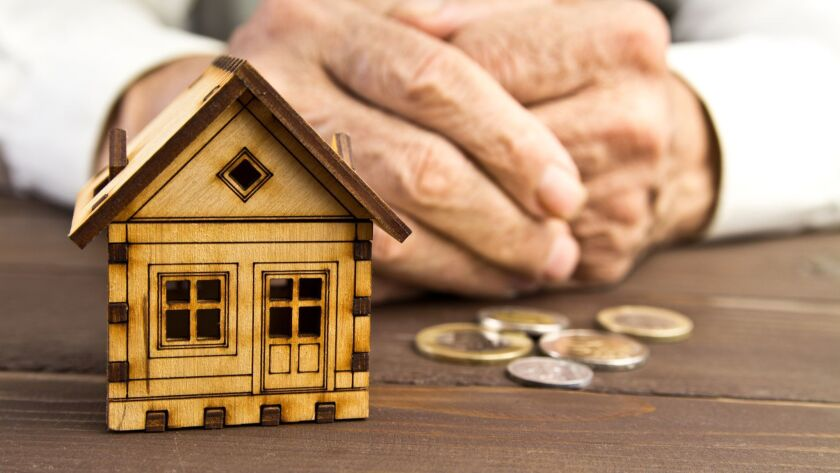 Old man hands and a model home with the coins on the table .The concept of mortgages and Bank loans, housing loans. Poverty.