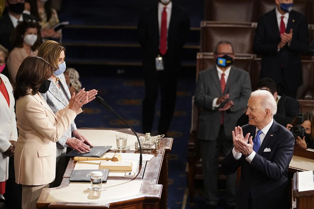President Biden faces two women on a dais.