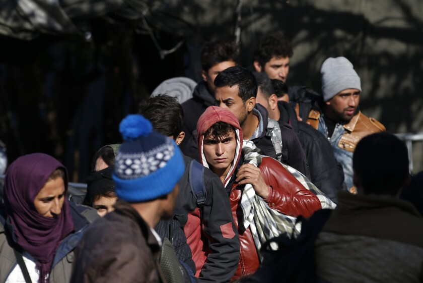 Syrian migrants wait to register with the police at the refugee center in the southern Serbian town of Presevo.