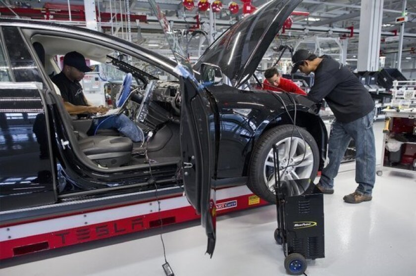 Tesla Motor Inc. associates work on the Model S electric car at the company's factory in Fremont, Calif. North American auto production will near 15-year high by 2015, but auto factory jobs won't return to pre-recession levels even by then.
