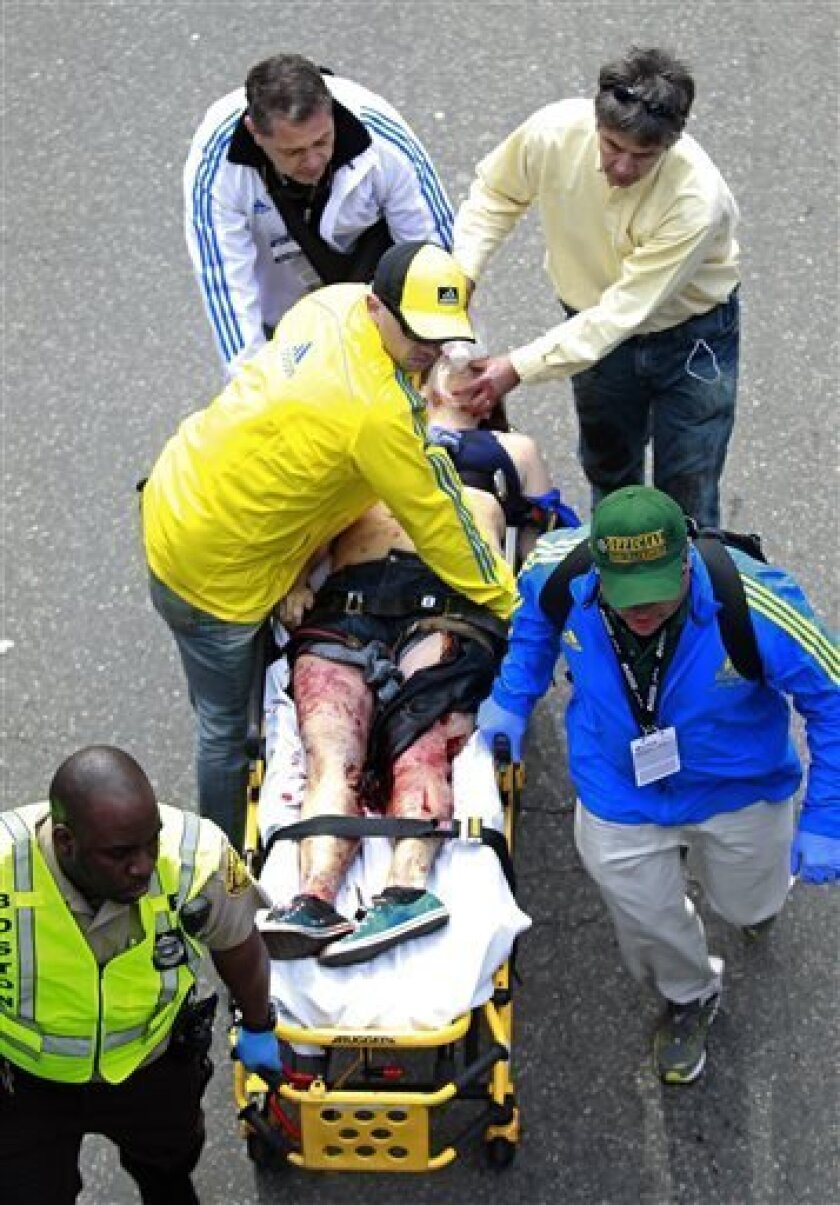 Medical workers aid an injured man at the finish line of the 2013 Boston Marathon following an explosion in Boston, Monday, April 15, 2013. Two bombs exploded near the finish of the Boston Marathon on Monday, killing two people, injuring 22 others and sending authorities rushing to aid wounded spec