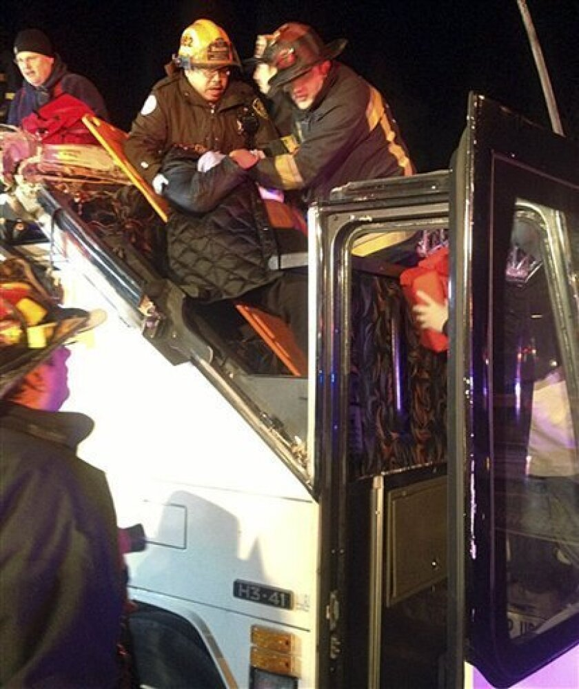 In this photo released by the Boston Fire Department via Twitter, firemen work to remove injured passengers from a bus that hit an bridge as it traveled along Soldiers Field Road in the Allston neighborhood of Boston Saturday night, Feb. 2, 2013. Officials said the bus carryinyg 42 people was trave
