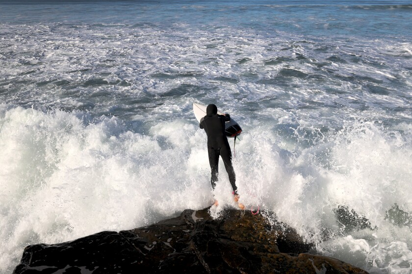 A surfer jumps into the surf at Sunset Cliffs as large waves pound the San Diego coastline.