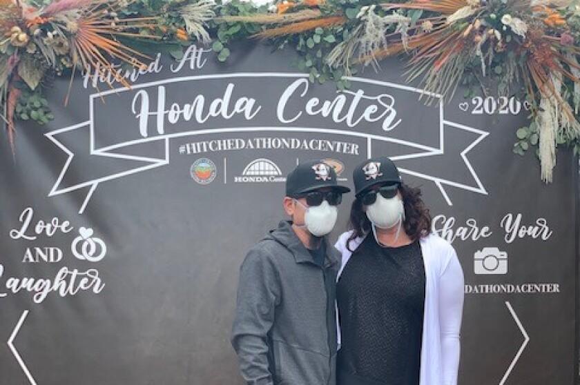 "Wearing matching Ducks hats and surgical masks, Jayson Furusawa and Lynsey Koopman recently got ""Hitched at Honda Center."""