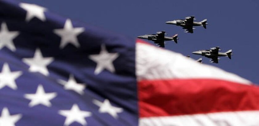 Four Marine Harrier jets, one hidden behind an American flag, during a ship flyover.
