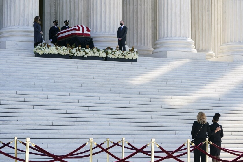 People pay respects as Justice Ruth Bader Ginsburg lies in repose under the Portico at the top of the front steps of the U.S. Supreme Court building on Wednesday, Sept. 23, 2020, in Washington. Ginsburg, 87, died of cancer on Sept. 18. (AP Photo/Patrick Semansky)