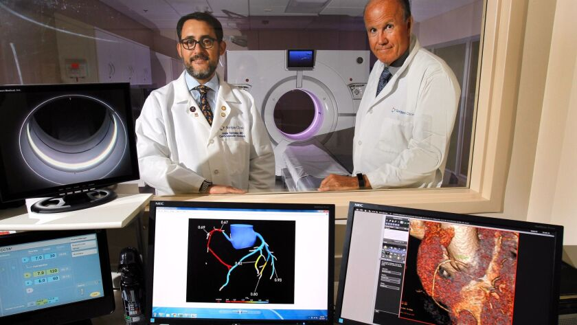 Dr. George Wesbey (right) Dr. Jorge Gonzalez stand with the digital heart models created by HeartFlow FFR, a new analytics system that uses high-resolution digital X-ray scans to model blood flow in the coronary arteries.